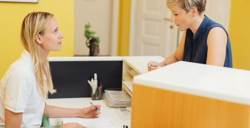 Female patient registering at a medical reception standing at the counter talking to the receptionist about her appointment